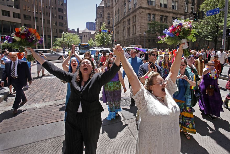 Nancy Janda, left, and her new spouse Larisa Van Winkle, right, parade through the streets of downtown Pittsburgh after being one of 19 same-sex couples married by Pittsburgh Mayor Bill Peduto in a marriage ceremony held in the Pittsburgh City Council chambers, Sunday, June 15, 2014. (AP Photo/Gene J. Puskar)