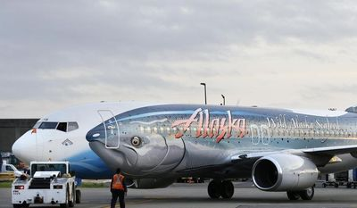 """** FILE ** The Alaska Airlines """"Salmon Thirty Salmon,"""" a Boeing 737 airplane painted to promote salmon and other seafood the airline's cargo division ships from Alaska, is moved to make room for another plane caring the first shipment of the year of Copper River salmon Friday, May 16, 2014, from Cordova, Alaska, in Seatac, Wash., near Seattle. (AP Photo/Ted S. Warren)"""