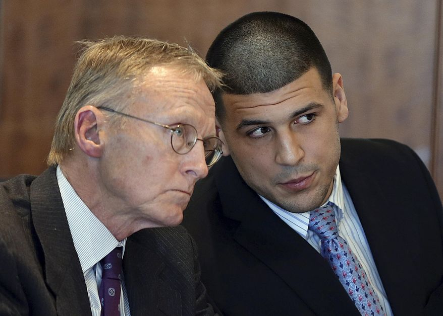 FILE - In this Friday, Feb. 7, 2014, file photo, former New England Patriots football player Aaron Hernandez, right, speaks to his attorney Charles Rankin during a hearing at Bristol Superior Court, in Fall River, Mass. Hernandez's lawyers are expected to ask a judge to dismiss the murder charge he faces in connection with last June's execution-style killing of Odin Lloyd in North Attleborough, Mass. (AP Photo/The Boston Globe, Jonathan Wiggs, Pool, File)
