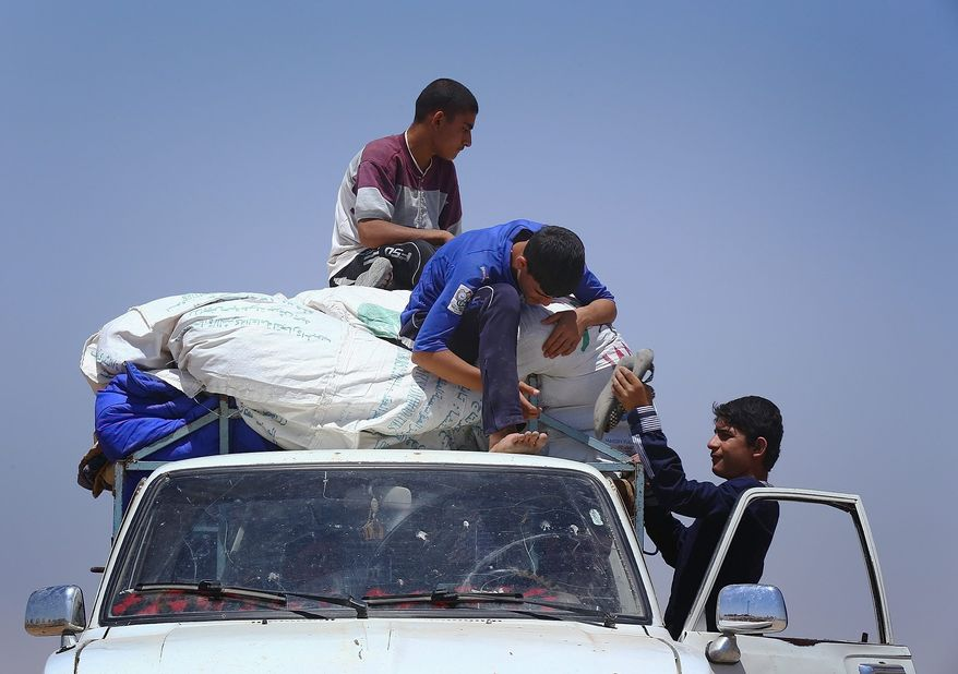 Iraqis who have fled the violence in their hometown of Mosul unload their car at Khazir refugee camp outside of Irbil, 217 miles north of Baghdad, Iraq, Monday. (associated press)