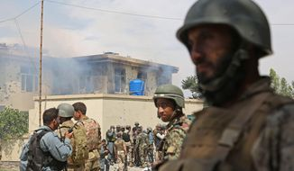 Afghan police officers arrive at the scene after Taliban fighters stormed a government building in Jalalabad, east of Kabul, Afghanistan, May 12, 2014. (Associated Press) ** FILE **