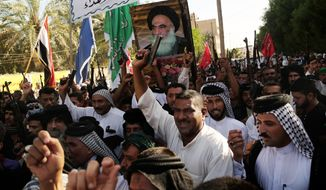 Shiite tribal fighters carry a poster of Shiite spiritual leader Grand Ayatollah Ali al-Sistani, as they raise their weapons chanting against the al Qaeda-inspired Islamic State of Iraq and the Levant (ISIL) in Basra, Iraq's second-largest city, 340 miles (550 kilometers) southeast of Baghdad, Iraq, Monday, June 16, 2014. (AP Photo/ Nabil Al-Jurani)