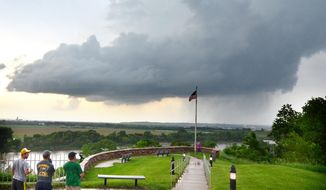Onlookers standing at the Sgt. Floyd Monument in Sioux City, Iowa, watch as a storm cell passes over the city Monday, June 16, 2014. (AP Photo/The Sioux City Journal, Tim Hynds)