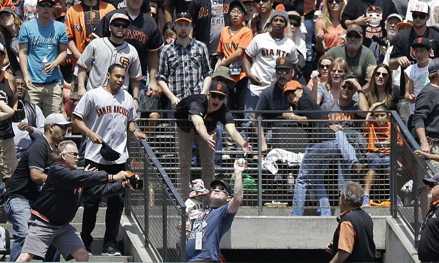 A fan holding a child, bottom, catches Colorado Rockies' Troy Tulowitzki's two-run home run against the San Francisco Giants during the third inning of a baseball game in San Francisco, Sunday, June 15, 2014. The Rockies won 8-7. (AP Photo/Jeff Chiu)