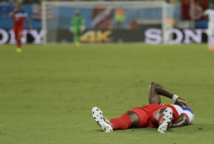 United States' Jozy Altidore holds his hand to his face as he lies on the pitch after pulling up injured during the group G World Cup soccer match between Ghana and the United States at the Arena das Dunas in Natal, Brazil, Monday, June 16, 2014. (AP Photo/Ricardo Mazalan)
