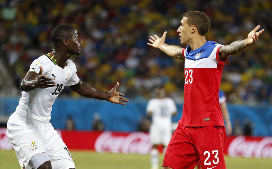 United States' Fabian Johnson, right, and Ghana's Jonathan Mensah question the referee's call during the group G World Cup soccer match between Ghana and the United States at the Arena das Dunas in Natal, Brazil, Monday, June 16, 2014. (AP Photo/Julio Cortez)