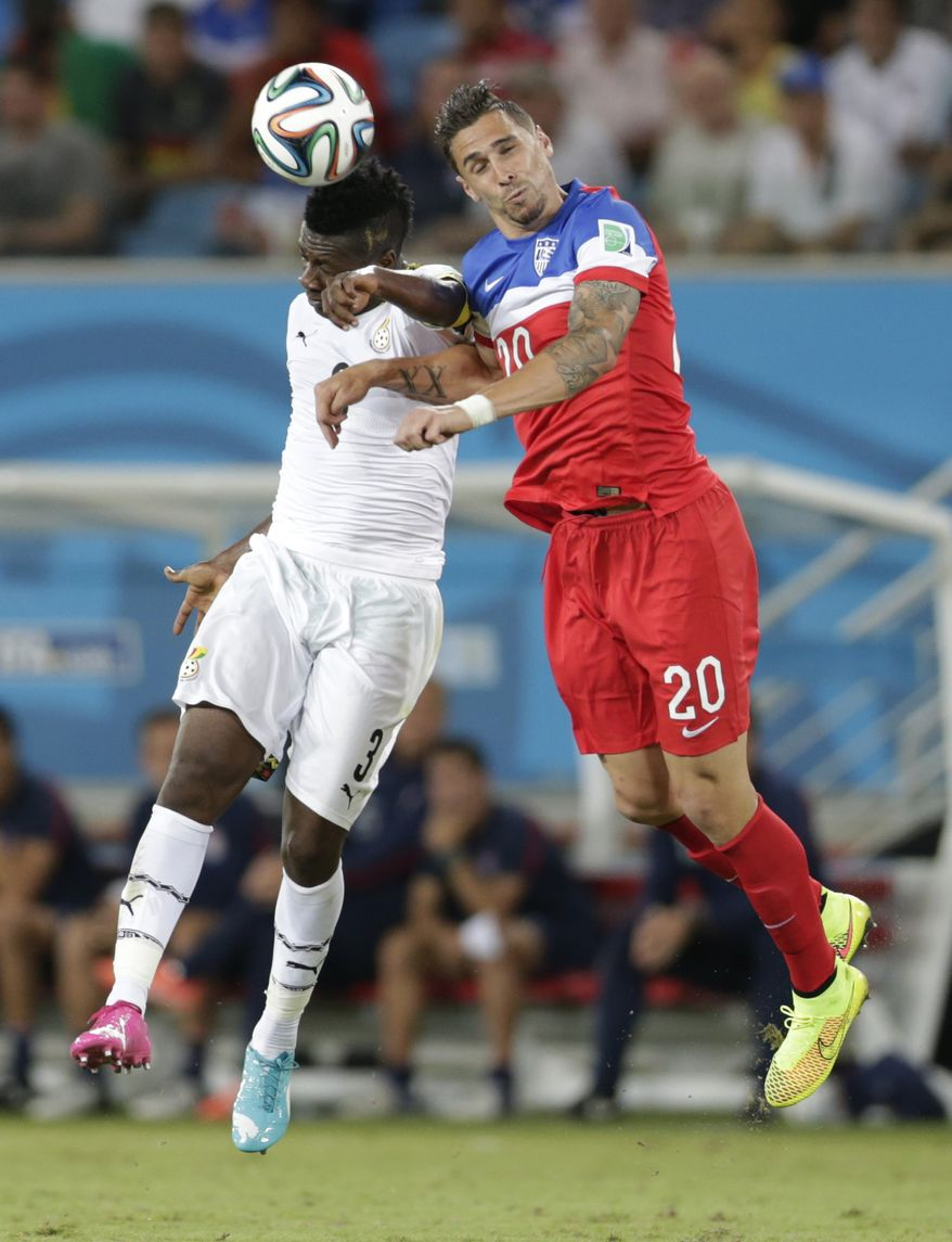 Ghana's Asamoah Gyan, left, and United States' Geoff Cameron jump to head the ball during the group G World Cup soccer match between Ghana and the United States at the Arena das Dunas in Natal, Brazil, Monday, June 16, 2014.  (AP Photo/Dolores Ochoa)