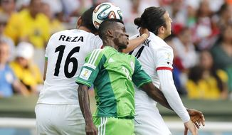 Nigeria's Ramon Azeez goes up against Iran's Reza Ghoochannejhad (16) and Andranik Teymourian during the group F World Cup soccer match between Iran and Nigeria at the Arena da Baixada in Curitiba, Brazil, Monday, June 16, 2014.  (AP Photo/Frank Augstein)