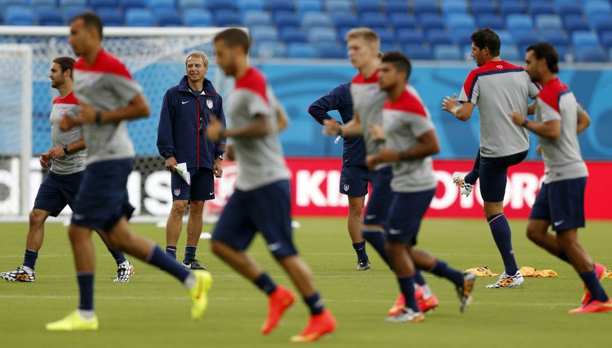 United States' head coach Jurgen Klinsmann, back left, looks on as his team warms up during an official training session the day before the group G World Cup soccer match between Ghana and the United States at the Arena das Dunas in Natal, Brazil, Sunday, June 15, 2014.  (AP Photo/Julio Cortez)