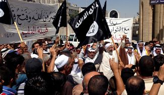 Demonstrators chant pro-al-Qaida-inspired Islamic State of Iraq and the Levant (ISIL) as they wave al-Qaida flags in front of the provincial government headquarters in Mosul, 225 miles (360 kilometers) northwest of Baghdad, Iraq, Monday, June 16, 2014. Sunni militants captured a key northern Iraqi town along the highway to Syria early on Monday, compounding the woes of Iraq's Shiite-led government a week after it lost a vast swath of territory to the insurgents in the country's north. (AP Photo)