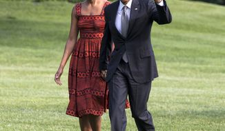 President Barack Obama waves as he walks with first lady Michelle Obama on their return to the White House from a trip to California, Monday, June 16, 2014, in Washington. (AP Photo/Jacquelyn Martin)