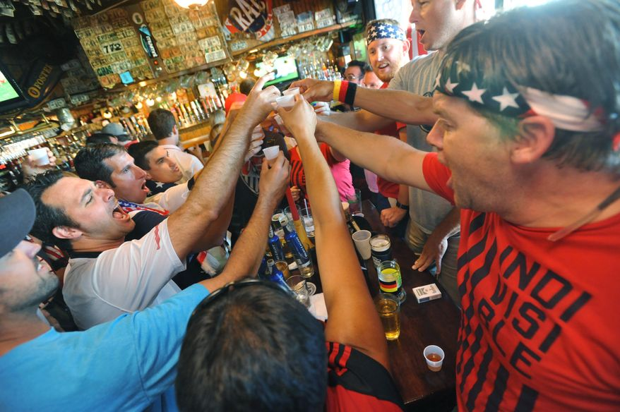 Soccer fans celebrate after the USA scores a goal early in their World Cup match against Ghana Monday, June 16, 2014 at Lynch's Irish Pub in Jacksonville Beach, Fla. (AP Photo/The Florida Times-Union, Will Dickey)