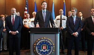FBI Director James Comey, backed by law enforcement personnel and prosecutors, addresses a news conference Tuesday, June 17, 2014 at the FBI Minneapolis field office in Brooklyn Center, Minn. Comey said the arrest Sunday of a Libyan militant in the deadly attack on Americans in Benghazi is a very good day for law enforcement and added that the FBI's No. 1 priority remains counterterrorism. (AP Photo/Jim Mone)