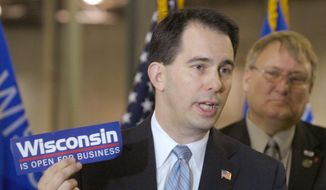 ** FILE ** In this March 17, 2011, file photo Wisconsin Gov. Scott Walker holds a bumper sticker with his signature campaign promise for the state as he announces a new  manufacturer will move to Pleasant Prairie, near Kenosha, Wis. (AP Photo/Journal Times, Mark Hertzberg, File)