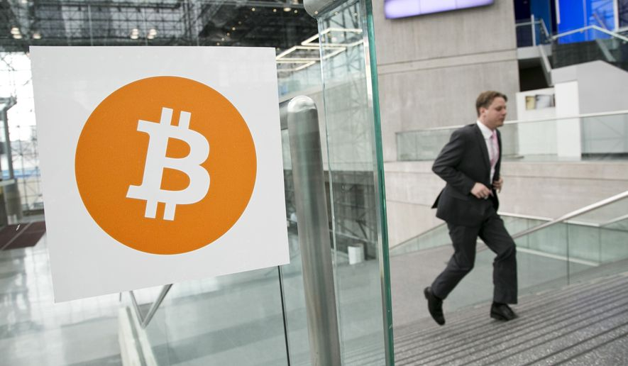 In this April 7, 2014, file photo, a man arrives for the Inside Bitcoins conference and trade show in New York. The Bitcoin digital currency system is in danger of losing its credibility as an independent payment system because of the growing power of a group that runs the some of the computers behind it. (AP Photo/Mark Lennihan, File)