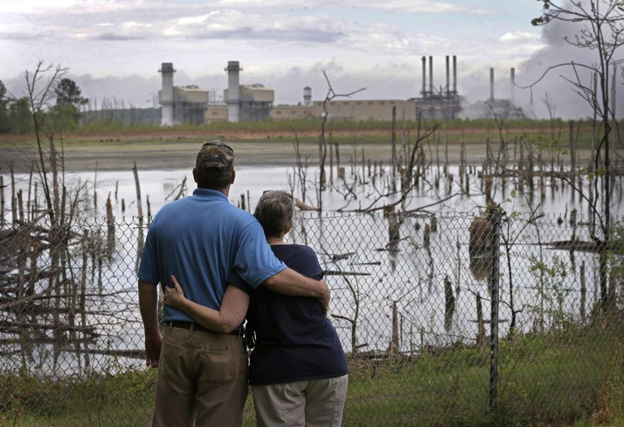 In this April 25, 2014, photo, Bryant Gobble, left, hugs his wife, Sherry Gobble, right, as they look from their yard across an ash pond full of dead trees toward Duke Energy's Buck Steam Station in Dukeville, N.C. (AP Photo/Chuck Burton)