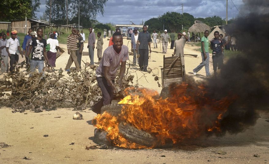 Residents barricade a road with burning tires and other roadblocks as they protest against the recent killings and what they claimed was the government's failure to provide them with enough security, in the village of Kibaoni just outside the town of Mpeketoni, about 60 miles (100 kilometers) from the Somali border on the coast of Kenya Tuesday, June 17, 2014. (AP Photo)