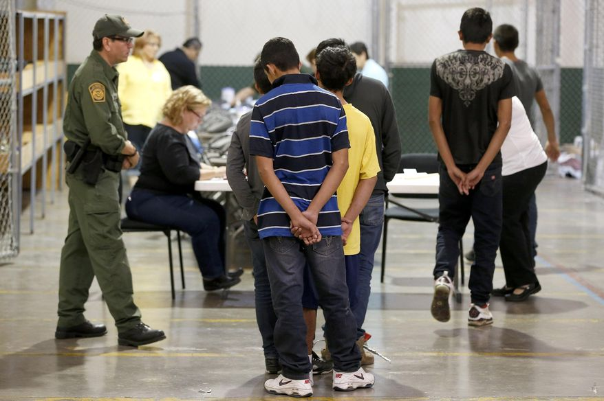Boys wait in line to make a phone call as they are joined by hundreds of mostly Central American immigrant children that are being processed and held at the U.S. Customs and Border Protection Nogales Placement Center on Wednesday, June 18, 2014, in Nogales, Ariz.  CPB provided media tours Wednesday of two locations in Brownsville, Texas, and Nogales, that have been central to processing the more than 47,000 unaccompanied children who have entered the country illegally since Oct. 1. (AP Photo/Ross D. Franklin, Pool)