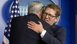 White House Chief of Staff Dennis McDonough hugs outgoing White House press secretary Jay Carney at the end of his last briefing as secretary, Wednesday, June 18, 2014,  in the press briefing room of the White House in Washington. (AP Photo/Jacquelyn Martin)