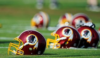"FILE - In this June 17, 2014, file photo, Washington Redskins helmets sit on the field during an NFL football minicamp in Ashburn, Va. The U.S. Patent Office ruled Wednesday, June 18, 2014, that the Washington Redskins nickname is ""disparaging of Native Americans"" and that the team's federal trademarks for the name must be canceled. The ruling comes after a campaign to change the name has gained momentum over the past year. (AP Photo/Nick Wass, File)"