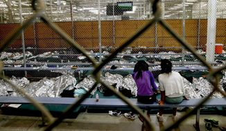 Two young girls watch a World Cup soccer match on a television from their holding area where hundreds of mostly Central American immigrant children are being processed and held at the U.S. Customs and Border Protection Nogales Placement Center on Wednesday, June 18, 2014, in Nogales, Ariz.  CPB provided media tours Wednesday of two locations in Brownsville, Texas, and Nogales, that have been central to processing the more than 47,000 unaccompanied children who have entered the country illegally since Oct. 1. (AP Photo/Ross D. Franklin, Pool)