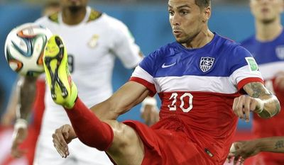 United States' Geoff Cameron, left, kicks the ball clear from Ghana's Andre Ayew during the group G World Cup soccer match between Ghana and the United States at the Arena das Dunas in Natal, Brazil, Monday, June 16, 2014.  (AP Photo/Ricardo Mazalan)