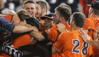 Virginia players celebrate a 3-2 win over TCU in 15 inning in an NCAA baseball College World Series game in Omaha, Neb., Tuesday, June 17, 2014. (AP Photo/Eric Francis)