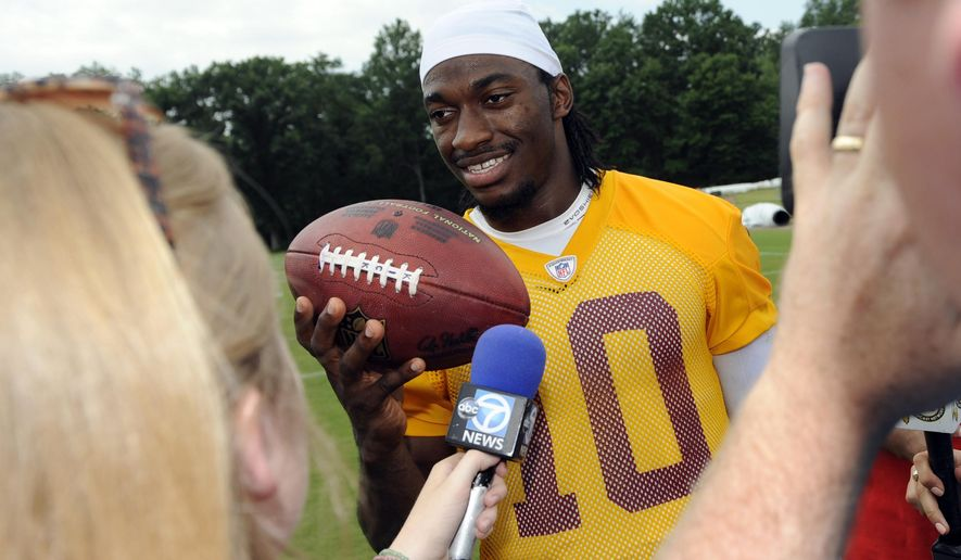 Washington Redskins quarterback Robert Griffin III speaks with the media after NFL football minicamp, Wednesday, June 18, 2014, in Ashburn, Va. (AP Photo/Nick Wass)