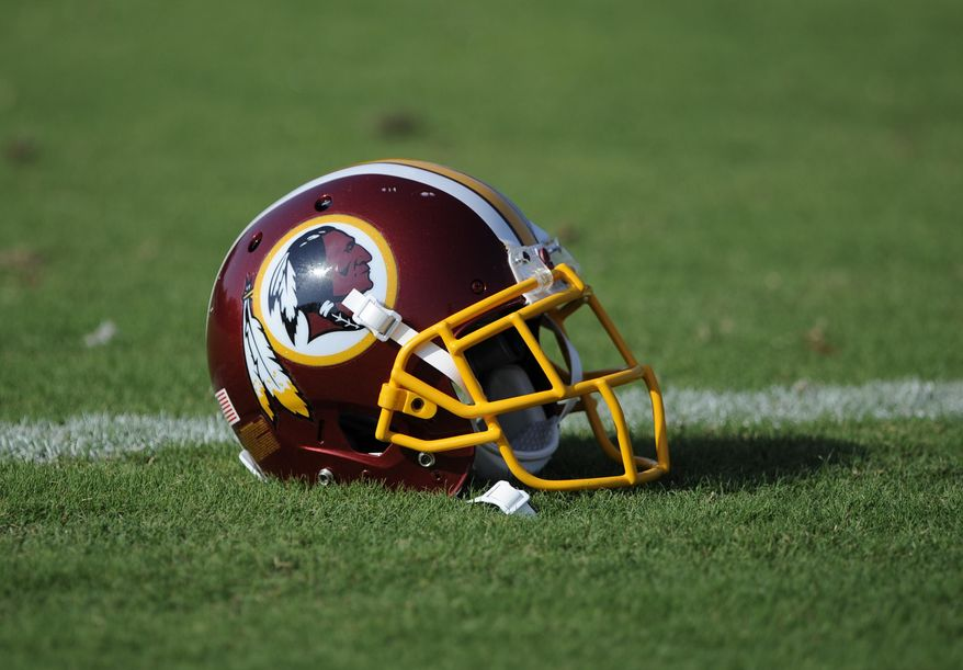 "A Washington Redskins football helmet lies on the field during NFL football minicamp, Wednesday, June 18, 2014, in Ashburn, Va. The U.S. Patent Office ruled Wednesday, June 18, 2014, that the Washington Redskins nickname is ""disparaging of Native Americans"" and that the team's federal trademarks for the name must be canceled. The ruling comes after a campaign to change the name has gained momentum over the past year.  (AP Photo/Nick Wass)"