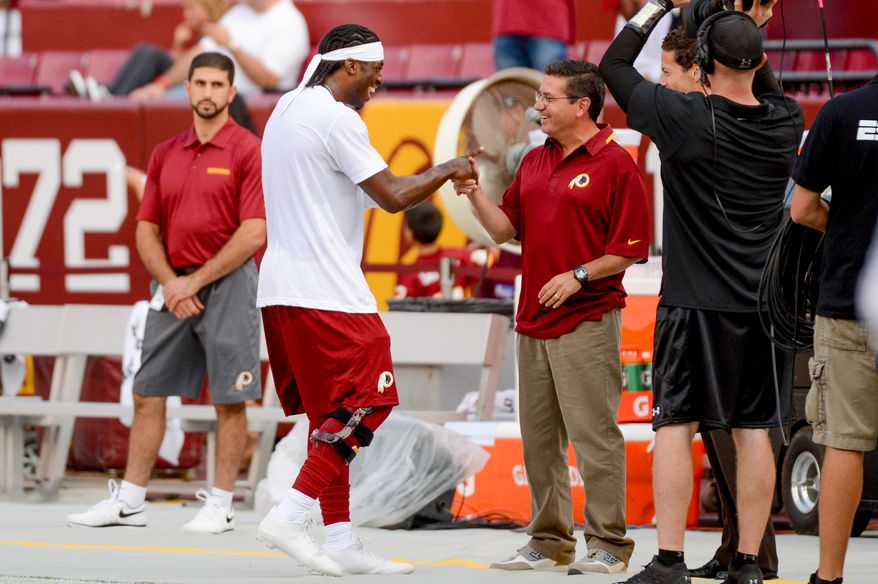Washington Redskins quarterback Robert Griffin III (10), center left, greets Washington Redskins owner Dan Snyder, center right, during warm ups before the Washington Redskins play the Pittsburgh Steelers in NFL preseason football at FedEx Field, Landover, Md., Monday, August 19, 2013. (Andrew Harnik/The Washington Times) **FILE**