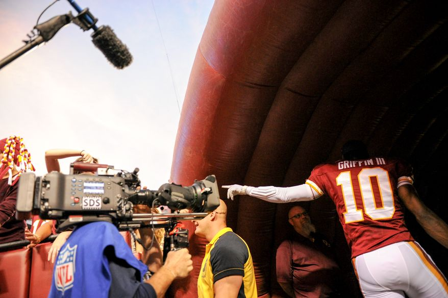 Washington Redskins quarterback Robert Griffin III (10) points to a fan before the Washington Redskins play the Pittsburgh Steelers in NFL preseason football at FedEx Field, Landover, Md., Monday, August 19, 2013. (Andrew Harnik/The Washington Times)