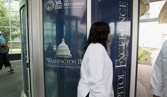 **FILE** People walk past the entrance of the Washington VA Medical Center in Washington on June 18, 2014. (Associated Press)