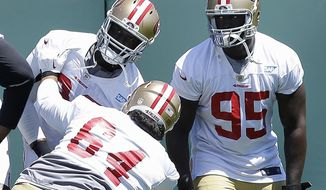 San Francisco 49ers defensive end Tank Carradine (95) watches as nose tackle Mike Purcell (64) practices against Quinton Dial during NFL football minicamp in Santa Clara, Calif., Thursday, June 19, 2014. (AP Photo/Jeff Chiu)