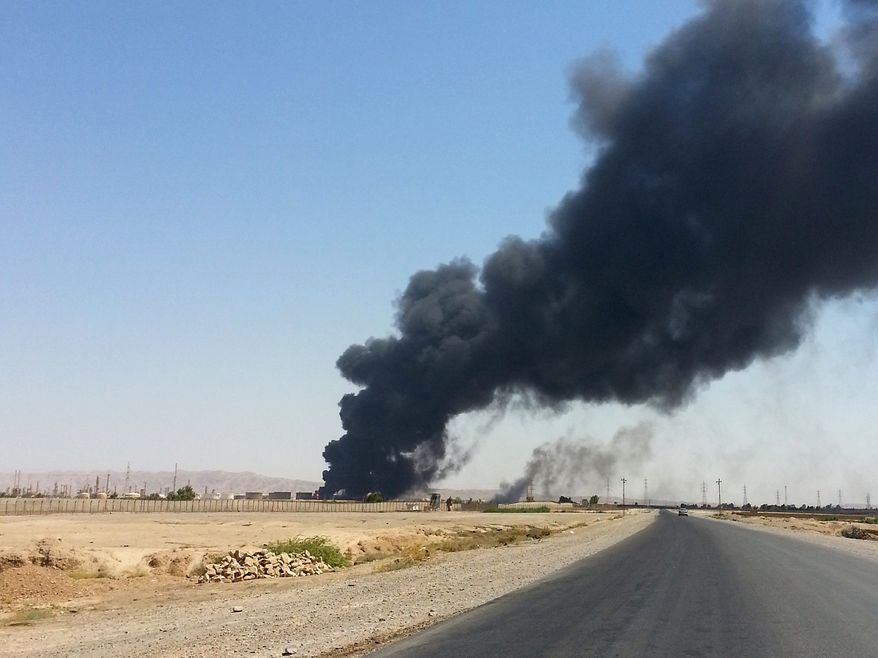 A column of smoke rises from an oil refinery in Baiji, 155 miles north of Baghdad, on Thursday. Sunni Muslim extremists who have taken over large portions of northern Iraq have shown their willingness to use oil supplies as a weapon. (Associated Press)