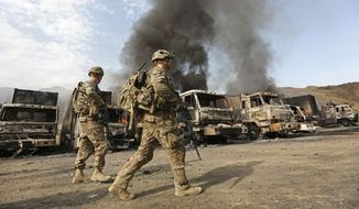 U.S. soldiers investigate the scene of an suicide attack in the Torkham, Nangarhar province, Afghanistan, on June 19. Afghan officials say three Taliban suicide bombers targeted NATO fuel trucks at the border with Pakistan, setting off a gunbattle with police guards. (Associated Press)