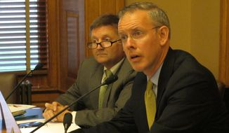 **FILE** Kansas House Minority Leader Paul Davis, right, a Lawrence Democrat, asks questions about plans to shift $675 million among various government accounts so that the state can pay its bills on time over the next year, Thursday, June 19, 2014, at the Statehouse in Topeka, Kan. Gov. Sam Brownback and legislative leaders, including Davis, have signed off on those plans. (AP Photo/John Hanna)