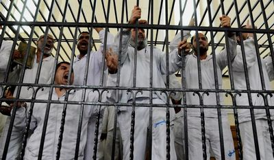 ** FILE **  Supporters of Egypt's ousted President Mohammed Morsi charged with violence chant slogans against the Egyptian military during a trial in court in Alexandria, Egypt, In this file photo taken March 29, 2014. (AP Photo/Heba Khamis, File)