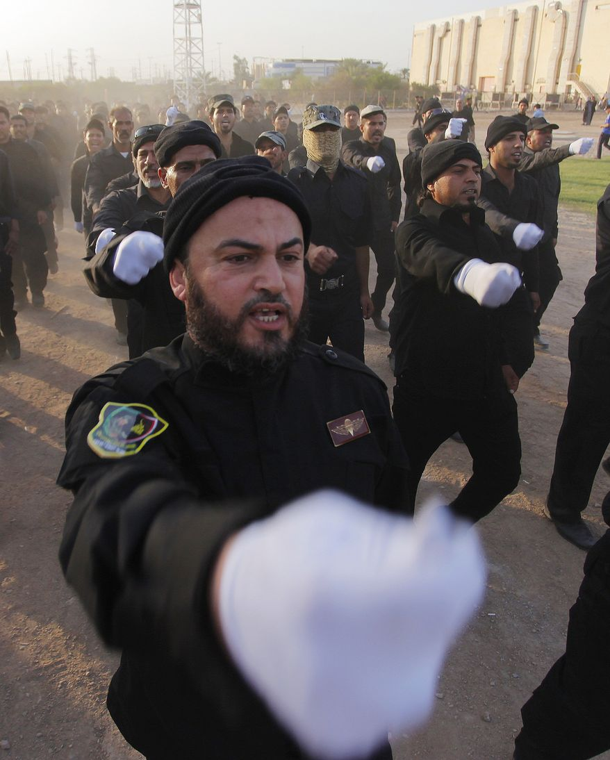 """Volunteers in the newly formed """"Peace Brigades"""" participate in a parade near the Imam Ali shrine in the southern holy Shiite city of Najaf, Iraq, Thursday, June 19, 2014, after called for by the radical Shiite cleric Muqtatda al-Sadr to form brigades to protect Shiite holy shrines against possible attacks by Sunni militants. (AP Photo/Jaber al-Helo)"""