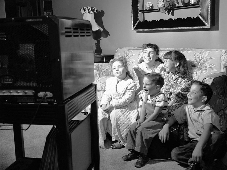 3. TELEVISION Like thousands of other children in this new video era, these youngsters sit in front of a television set and enjoy a program, Oct. 4, 1949. Television has brought parents problems, as well as blessings. The girls in the audience are left to right: Toni and Gail Herzog, Jerry Rose. The boys are the Grossi brothers, Ronnie, left, and Dennis. (AP Photo/Dan Grossi)