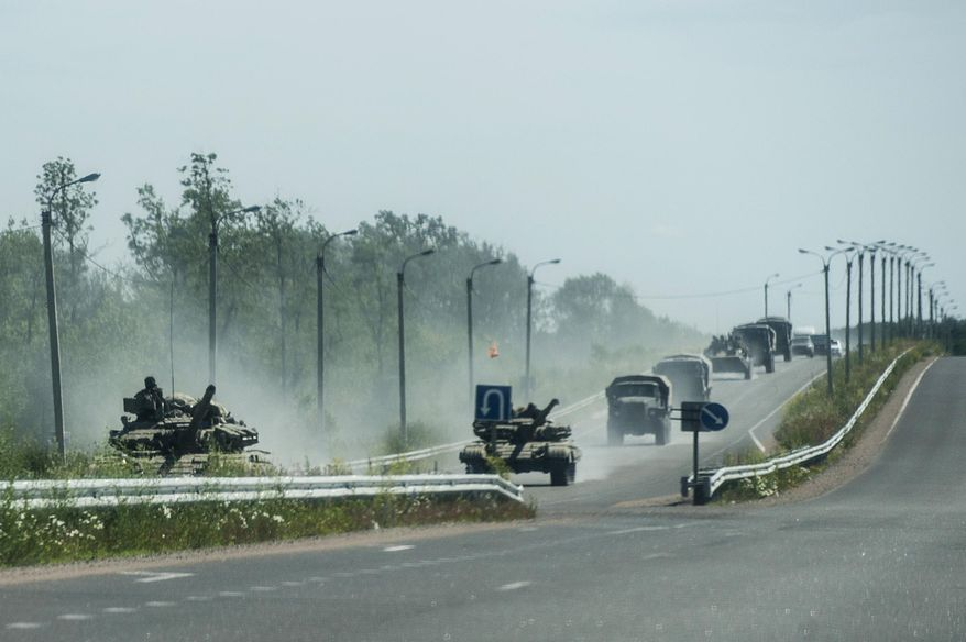 Pro-russian troops in tanks, several armored vehicles, and tracks drive on a road in the direction of Donetsk not far from Debaltseve, Donetsk region, eastern Ukraine, Friday, June 20, 2014. (AP Photo/Evgeniy Maloletka)