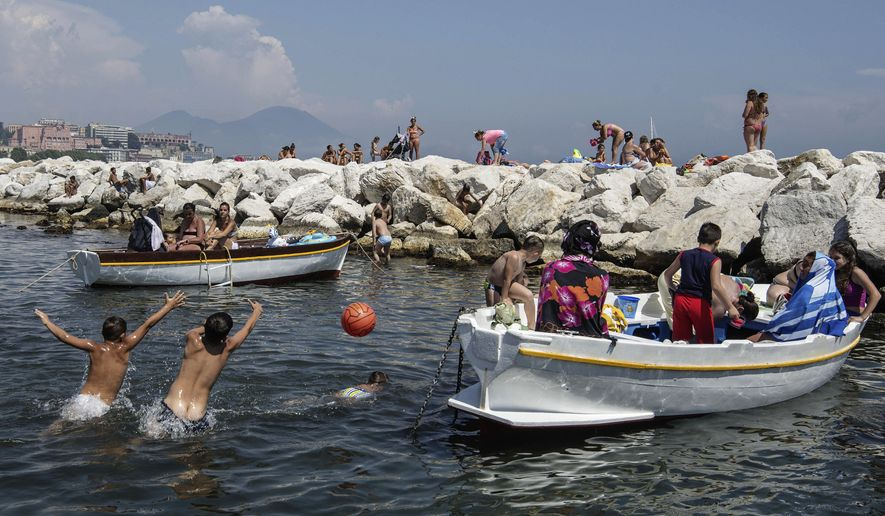 In this Friday, June 13, 2014 photo, people enjoy the sun and water at Mergellina bay, in Naples, Italy. Three years ago Naples' seafront was an urban highway, noisy and smoggy, jammed with car traffic, while smelly trash erupted from garbage bins along streets and alleys. Urban cyclers were regarded as eco-fundamentalists. Three years later, Naples has a new mayor, clean streets, a wide pedestrian beachfront and a 20-kilometer (20-mile) cycling lane overlooking a beautiful bay.  (AP Photo/Salvatore Laporta)