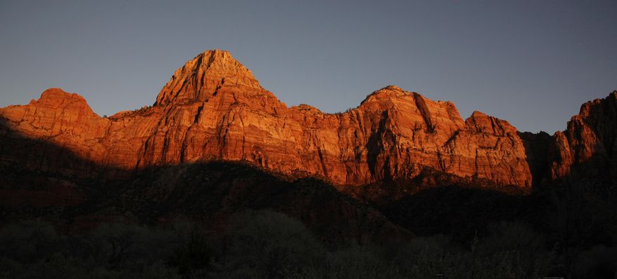 FILE - This Jan. 20, 2011 file photo shows shadows creeping up on sandstone cliffs glowing red as the sun sets on Zion National Park near Springdale, Utah. The National Park Service is taking steps to ban drones from 84 million acres of public lands and waterways, saying the unmanned aircraft annoy visitors, harass wildlife and threaten safety. Jonathan Jarvis, the park service's director, told The Associated Press he was signing a policy memorandum on Friday directing superintendents of the service's 401 parks to write rules prohibiting the launching, landing or operation of unmanned aircraft in their parks.  (AP Photo/Julie Jacobson, file)