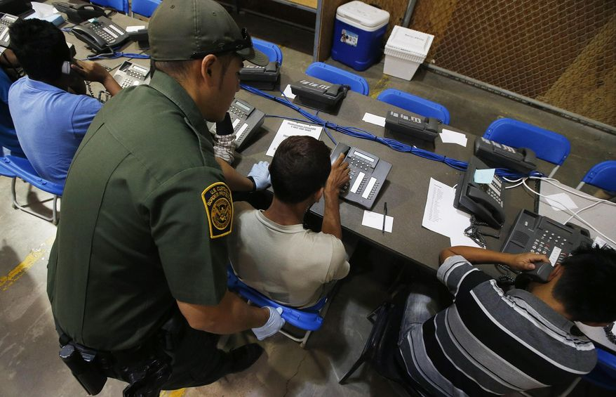 ** FILE ** This June 18, 2014, file photo shows a U.S. Customs and Border Protection officer as he helps a few boys to make phone calls, some of the hundreds of mostly Central American immigrant children that are being processed and held at the U.S. Customs and Border Protection Nogales Placement Center in Nogales, Ariz. (AP Photo/Ross D. Franklin, Pool, File)