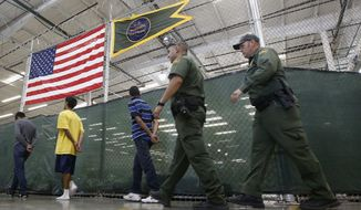 ** FILE ** This June 18, 2014, file photo shows young detainees being escorted to an area to make phone calls as hundreds of mostly Central American immigrant children are being processed and held at the U.S. Customs and Border Protection Nogales Placement Center in Nogales, Ariz. (AP Photo/Ross D. Franklin, Pool)