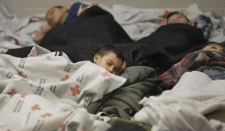 ** FILE ** This June 18, 2014, file photo shows children detainees sleeping in a holding cell at a U.S. Customs and Border Protection processing facility in Brownsville, Texas. (AP Photo/Eric Gay, Pool)