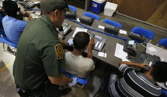 FILE - This June 18, 2014, file photo shows a U.S. Customs and Border Protection officer as he helps a few boys to make phone calls, some of the hundreds of mostly Central American immigrant children that are being processed and held at the U.S. Customs and Border Protection Nogales Placement Center in Nogales, Ariz. Thousands of immigrant children crossing alone into the U.S. can live in American cities, attend public schools and possibly work here for years without consequences. The chief reasons are an overburdened, deeply flawed system of immigration courts and a 2002 law intended to protect children's welfare, an Associated Press investigation finds. (AP Photo/Ross D. Franklin, Pool, File)