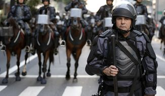 A Brazilian policeman leads a mounted unit as they follow about 300 protesters during a rally against the soccer World Cup in Sao Paulo, Brazil, Monday, June 23, 2014. (AP Photo/Thanassis Stavrakis)