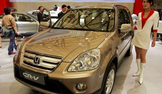 ** FILE ** In this April 21, 2005, file photo, a model poses by a Honda's CR-V at Auto Shanghai 2005 exhibition in Shanghai, China. Honda, Mazda and Nissan are recalling millions of vehicles globally for defective air bags manufactured by supplier Takata Corp. that could possibly explode. (AP Photo/Eugene Hoshiko, File)