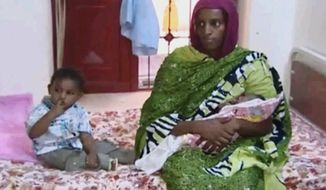 ** FILE ** In this file image made from an undated video provided Thursday, June 5, 2014, by Al Fajer, a Sudanese nongovernmental organization, Meriam Ibrahim, sitting next to Martin, her 18-month-old son, holds her newborn baby girl that she gave birth to in jail last week, as the NGO visits her in a room at a prison in Khartoum, Sudan. (AP Photo/Al Fajer, File)