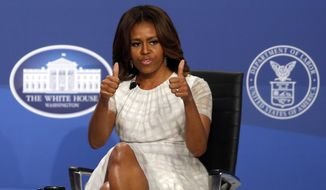 First lady Michelle Obama gives a thumbs up at The White House Summit on Working Families at a hotel in Washington, Tuesday, June 24, 2014. The gathering, organized by the White House, Department of Labor, and the Center for American Progress, highlights the challenges and offers solutions faced by working families in America. (AP Photo/Charles Dharapak)